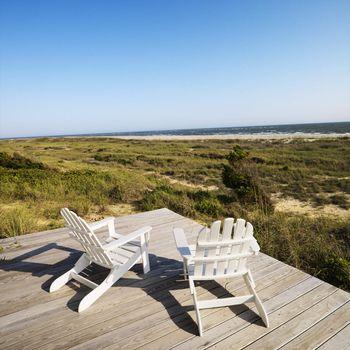 Two adirondack chairs on wooden deck overlooking beach at Bald Head Island, North Carolina.