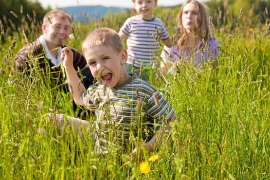 Very happy family with two kids sitting in a  meadow in the summer sun in front of a forest and hills, they are nearly hidden by the high grass, very peaceful scene