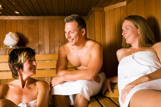 Three people (one male, two female) enjoying a hot sauna, talking to each other