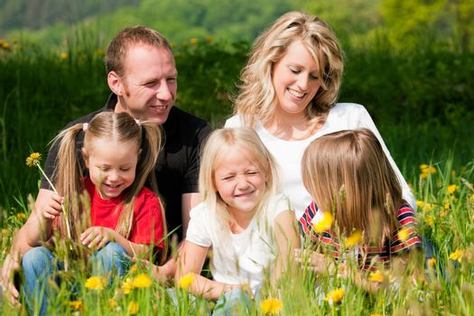 Very happy family with three kids sitting in a meadow with dandelion in the summer sun