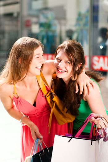 """Two women being friends shopping downtown with colorful shopping bags, in the background a store can be seen with the words """"sale"""" in the window"""