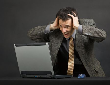 Нoung man shouts with despair looking at computer screen