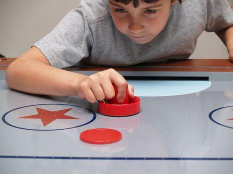 young boy playing air hockey