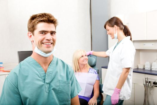 A happy smiling dentist at a clinic with an assistant and patient