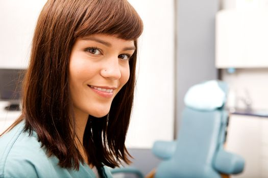A portrait of a dental hygienist in front of a dental chair