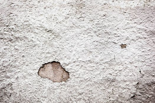 A weathered painted plaster wall that was once white