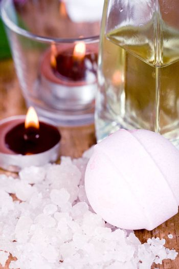 spa products (oil, salt, candles, ball) on wooden background