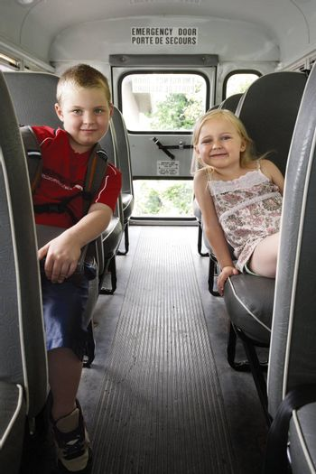 Photo of two happy children sitting in a school bus.