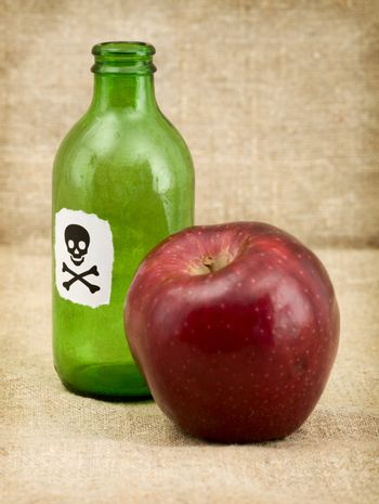 Bottle with poison and an apple
