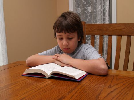 young boy sitting at a table and reading a book