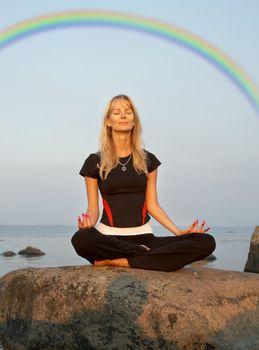 meditation at the seashore under rainbow