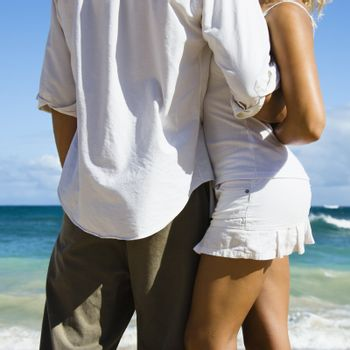 Attractive couple in embrace on Maui, Hawaii beach.