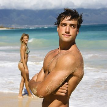 Handsome man standing on Maui, Hawaii beach with woman in background.