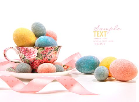 Brightly colored eggs in tea cup on white