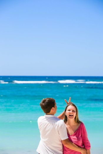 Young happy couple laughing. Man back turned to camera. Turquoise ocean on background.