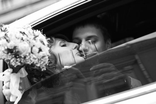 Newly-married couple in car with champagne