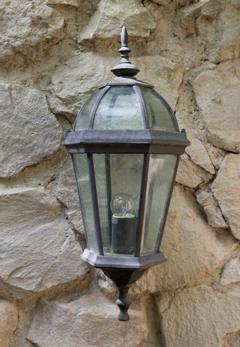 old lantern against stone wall