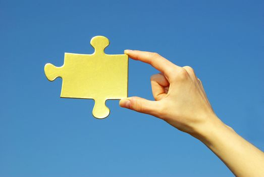 puzzle in hand isolated on blue background