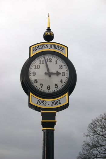 decorative clock against a cloudy sky