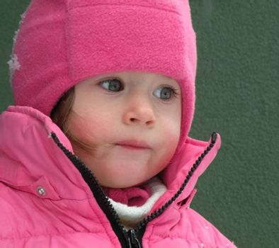 Beautiful children's face in winter with snow