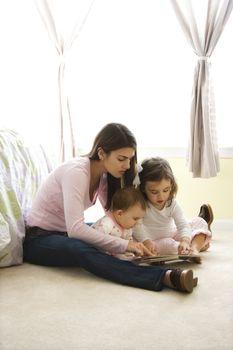 Caucasian girl children with mother sitting on bedroom floor looking at book.