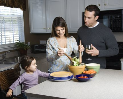 Caucasian woman making salad on kitchen counter with daughter and husband.
