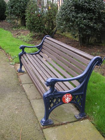 large wooden and cast-iron bench in a park
