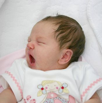 small newborn baby having a good yawn