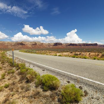 Utah landscape with distant mountains and two lane road.
