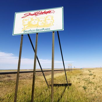 South Dakota road sign with Mount Rushmore graphic in rural field.