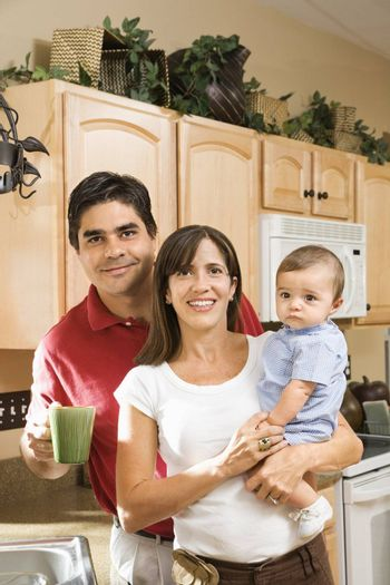 Hispanic family portrait in home kitchen with baby.