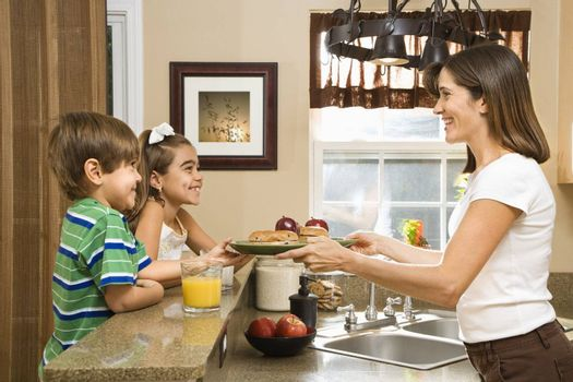 Hispanic mother handing healthy breakfast to young children in home kitchen.