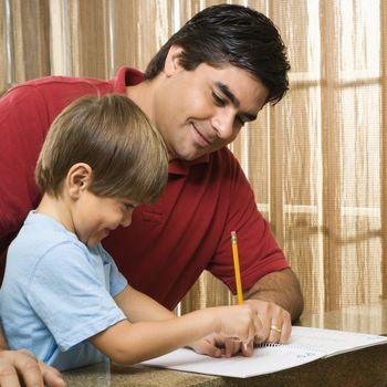Hispanic father helping son with homework.