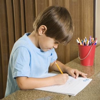 Side view of Hispanic boy concentrating on homework.