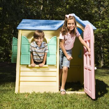 Hispanic boy and girl in outdoor playhouse smiling at viewer.