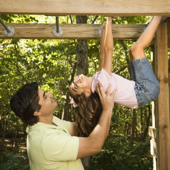 Hispanic girl hanging by arms and legs from monkey bars smiling at father helping her.