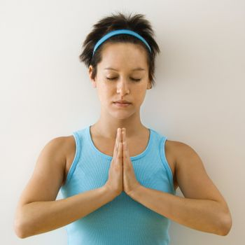 Young woman holding hands in prayer position with eyes closed meditating.