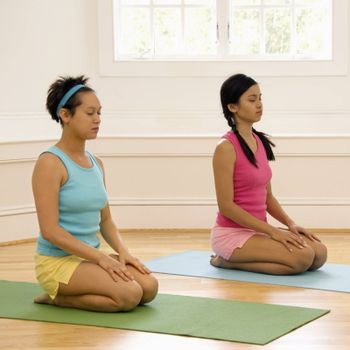 Two young women sitting on yoga mats with eyes closed.