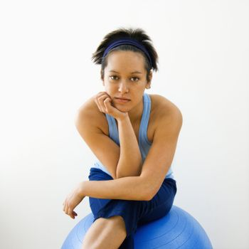 Portrait of young woman sitting on fitness balance ball.