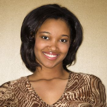 Close-up portrait of African-American young adult female smiling at viewer.