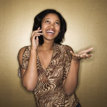 Young African-American young woman talking on cellphone smiling.