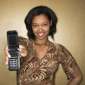 Young African-American young woman holding cellphone out to viewer.