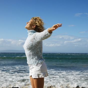 Pretty young blond woman standing on Maui, Hawaii beach with arms out to side and wind blowing hair smiling.