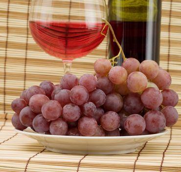 Glass bottle, goblet and grape