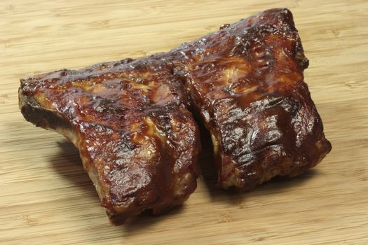 Grilled spare ribs on a wooden plate