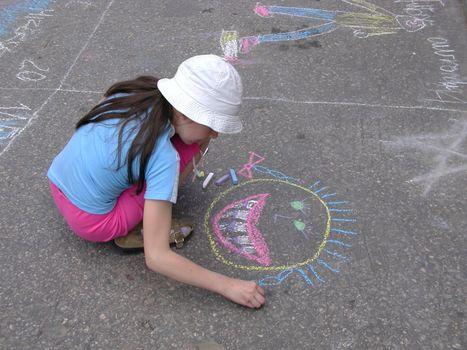 Girl drawing on asphalt