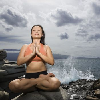 Asian woman sitting on rock by ocean in lotus pose with eyes closed in Maui, Hawaii