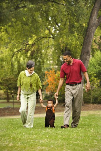 Mother and father helping toddler walk holding his hands in park.