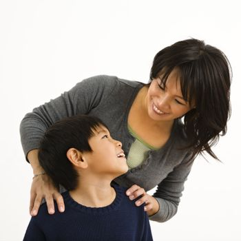Asian mother smiling at young son.