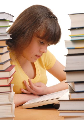 Teenage girl reading book and high book stacks on both sides